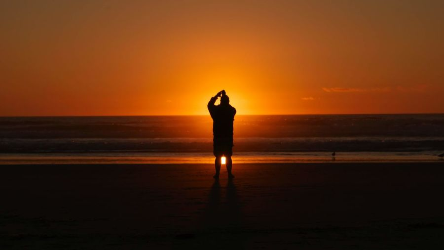 Silhouette standing on beach during sunset