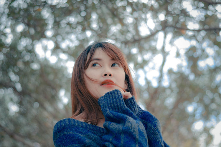 Beautiful woman in winter One Person Real People Tree Focus On Foreground Portrait Clothing Lifestyles Winter Young Women Young Adult Leisure Activity Women Hairstyle Front View Warm Clothing Scarf Headshot Looking At Camera Plant Sweater Hair Outdoors Bangs Beautiful Woman
