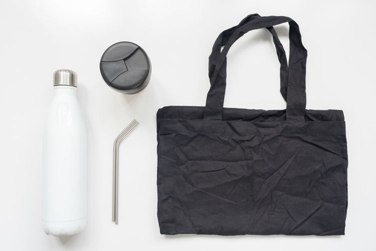 Zero waste shopping bag, drink bottle, travel mug and metal straws Still Life Indoors  Bottle No People Container White Background Table Studio Shot Close-up Black Color Leather Refreshment Fashion Directly Above Communication Food And Drink Zero Waste Lifestyle Sustainability Environmental Issues