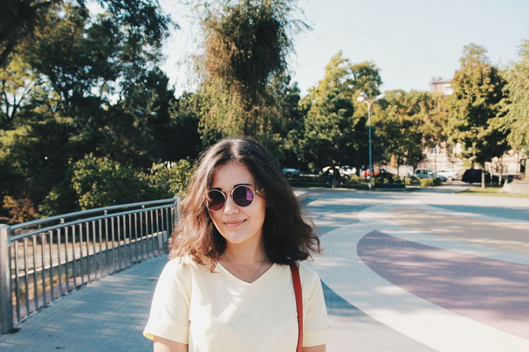 Portrait of woman in sunglasses standing on footpath against trees