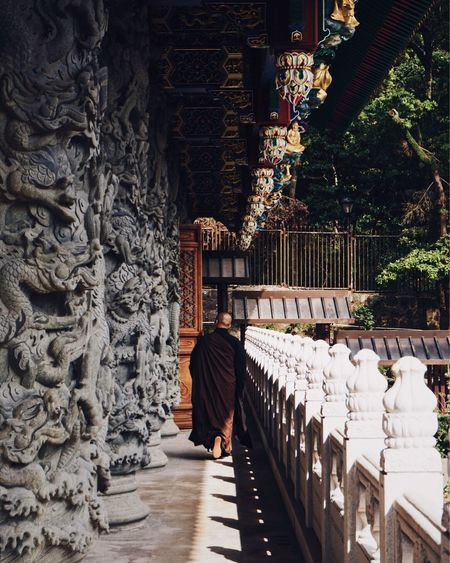 Rear view of monk wearing traditional clothing walking by temple