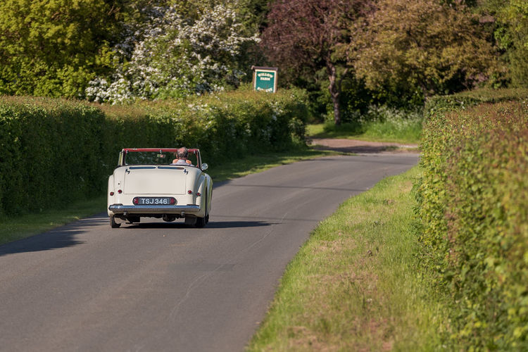A lone man drives his open top classic car along a summer hedgerow lined countryside road towards a bend. 2 Seater Activity Bend Classic Car Convertible Countryside Driver Driving Away Hedgerow Leisure Lined Man Open Top Restored Sunday Drive Transportation Plant Tree Mode Of Transportation Land Vehicle Road Motor Vehicle Day Sign Nature Green Color Car No People Direction The Way Forward Sunlight Travel Grass Outdoors on the move Road Trip