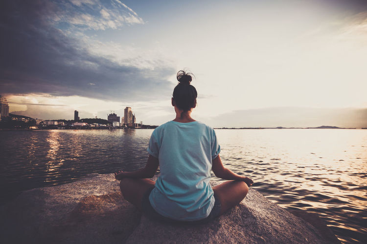 Rear view of woman meditating while sitting on rock in sea