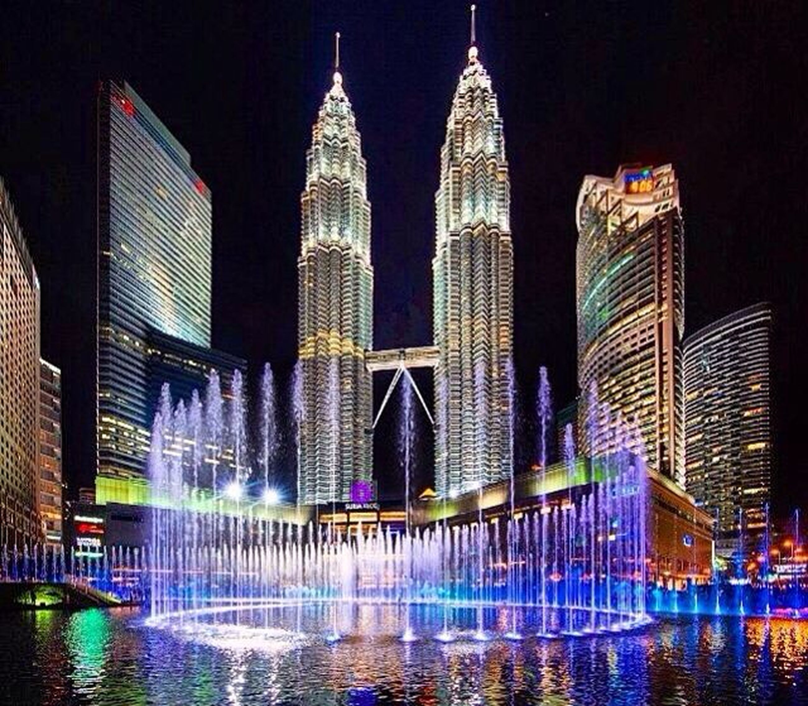 illuminated, skyscraper, water, building exterior, architecture, city, night, built structure, low angle view, modern, tall - high, multi colored, waterfront, travel destinations, tower, cityscape, fountain, tall, dark, tourism, spraying, city life, urban skyline, office building, famous place, outdoors, sky, capital cities