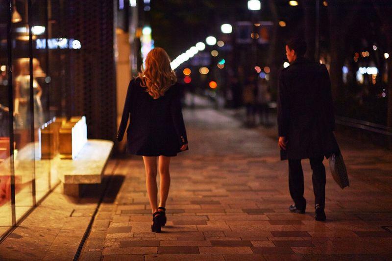 Rear view of business people walking on sidewalk at night