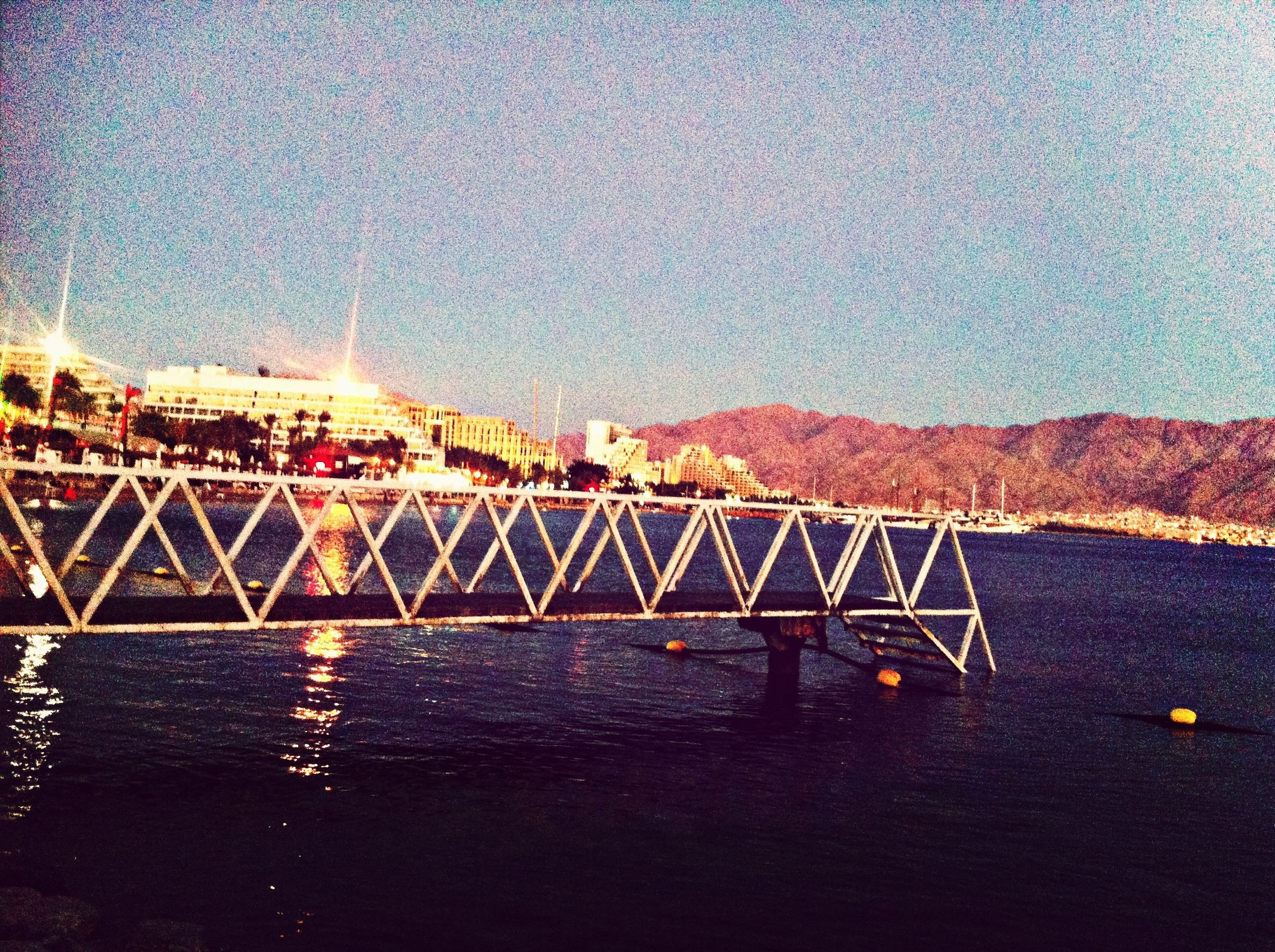water, built structure, bridge - man made structure, architecture, illuminated, connection, sky, sea, waterfront, river, bridge, night, engineering, copy space, clear sky, sunset, dusk, suspension bridge, transportation, outdoors