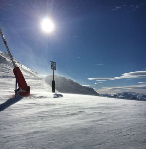 Man skiing on snow covered mountain against blue sky