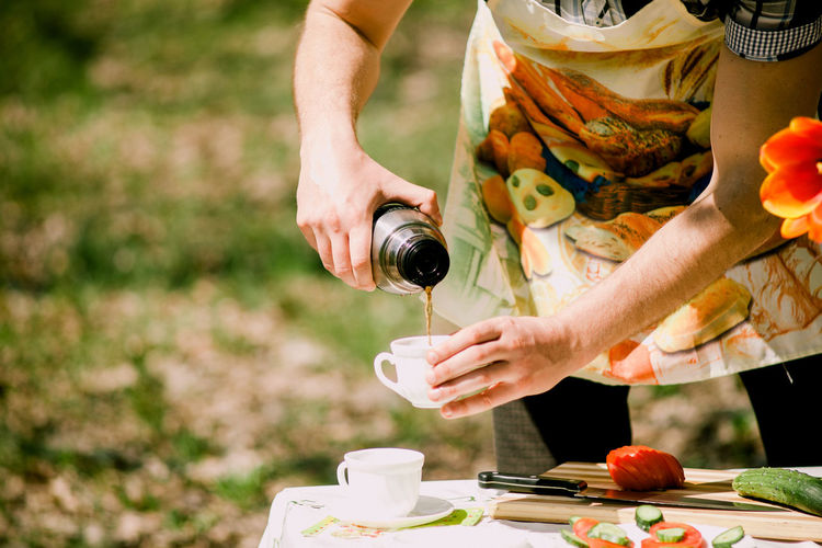Midsection of man pouring tea in cup outdoors