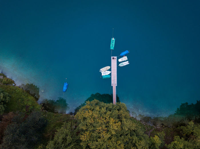 Aerial view of sailboats by pier in sea against trees