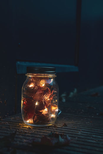 Close-up of illuminated glass jar on table