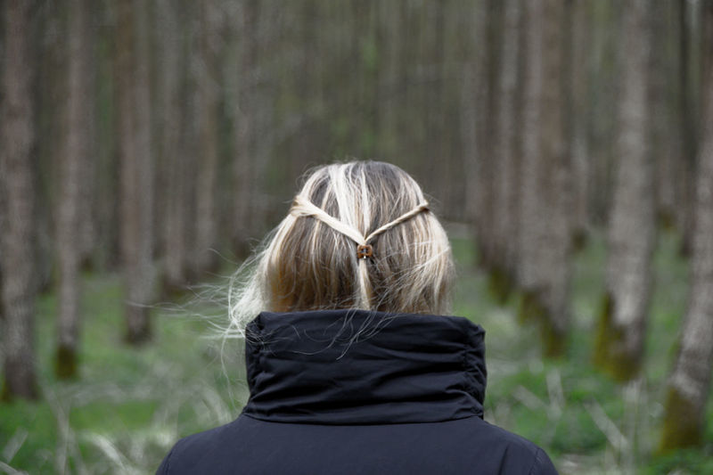 Rear View Of Woman In Warm Clothing Standing At Forest
