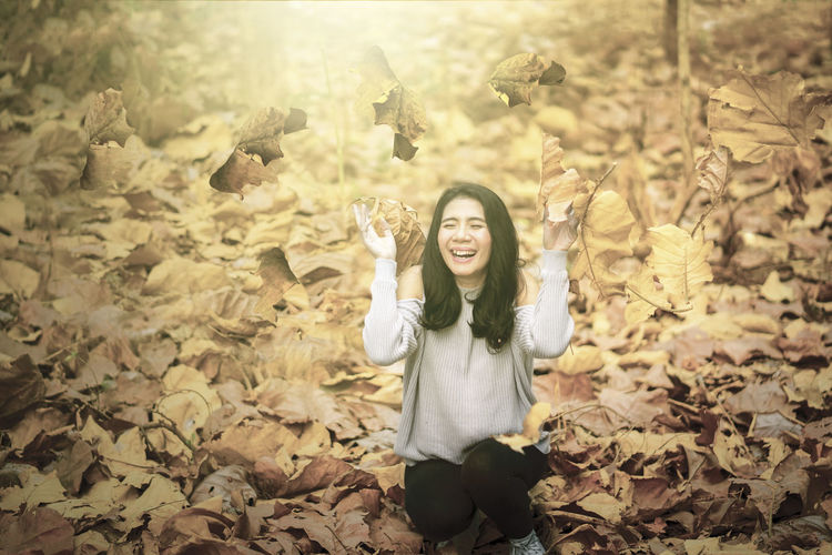 Portrait of smiling young woman standing by autumn leaves
