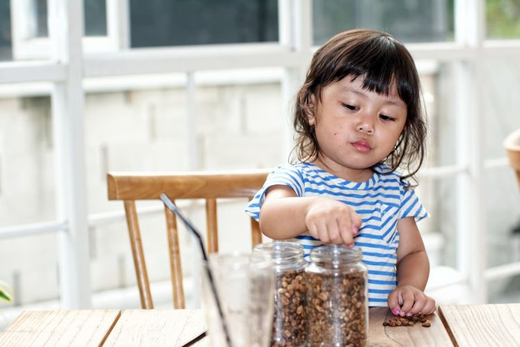 Close-up of girl with dried fruits in jar at table