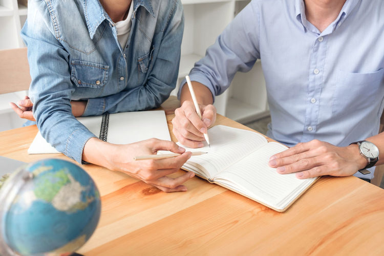 Midsection of business people discussing over diary at desk in office