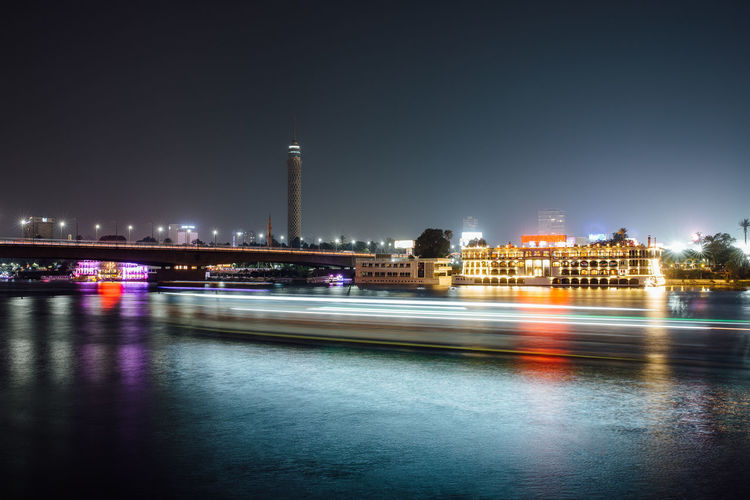 Cairo city center at night, long exposure with light trails of moving boats on the Nile river. Architecture Building Exterior Illuminated City Night Built Structure Building Water Long Exposure Sky Light Trail Travel Destinations Motion Office Building Exterior Waterfront Urban Skyline Reflection Landscape Cityscape Outdoors Government Cairo Egypt Zamalek