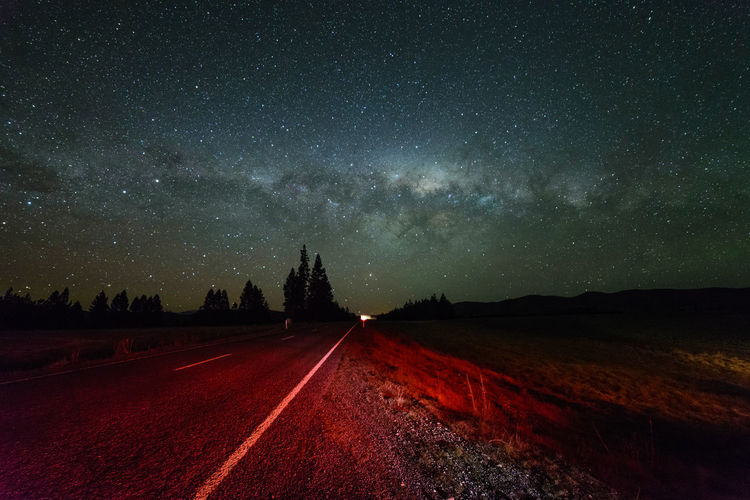 Milky way galaxy rising above rural road Astrology Sign Astronomy Beauty In Nature Constellation Galaxy Landscape Milky Way Nature Night No People Outdoors Sky Space Space And Astronomy Star - Space Star Field Tree
