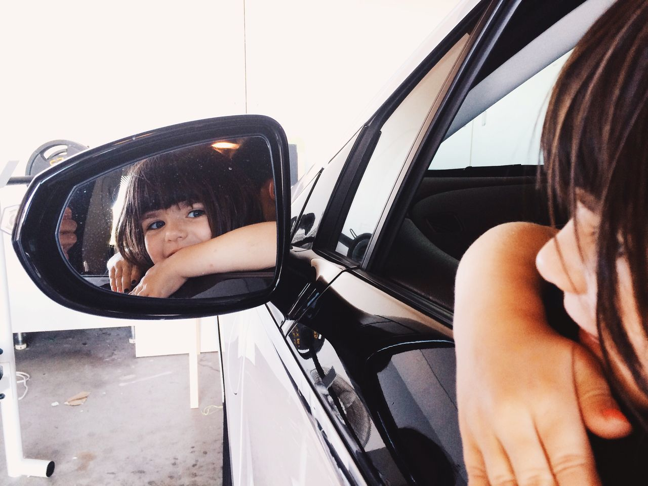 Smiling girl reflecting on side-view mirror