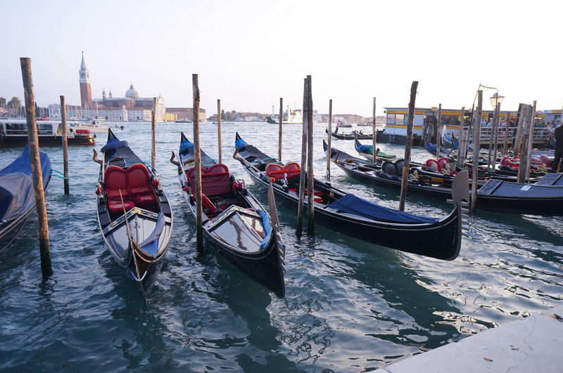 Gondolas moored by wooden post on grand canal against clear sky