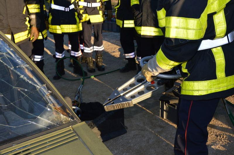 Firefighters against broken car in city