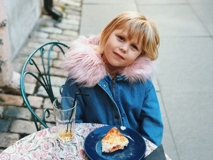 Portrait Of Smiling Cute Girl With Food Plate On Table Sitting At Sidewalk Cafe
