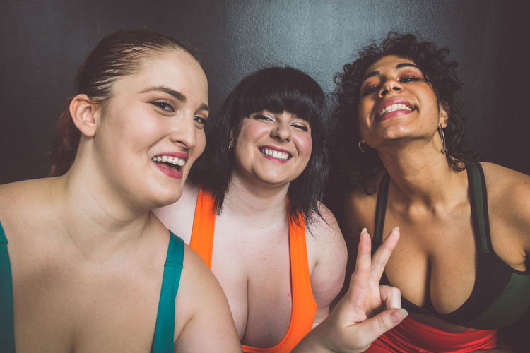 Smiling women standing against wall