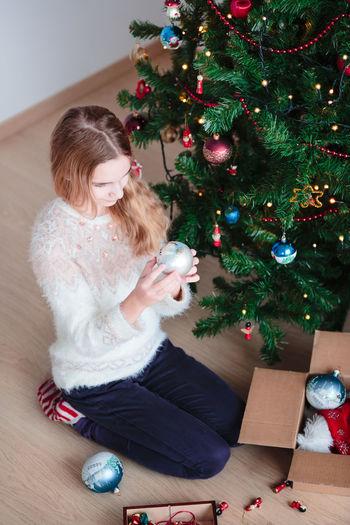 Full length of girl decorating christmas tree