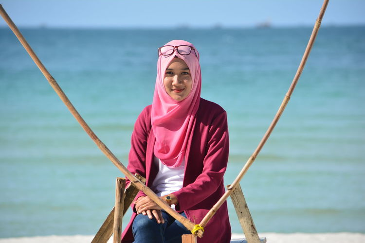 Portrait Of Smiling Woman Wearing Pink Hijab Sitting At Beach