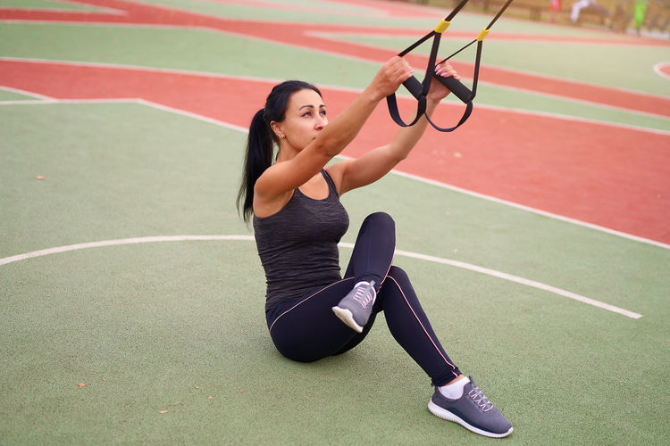 Woman exercising with equipment at court