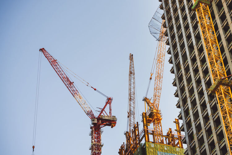 Low angle view of cranes on construction site against clear sky