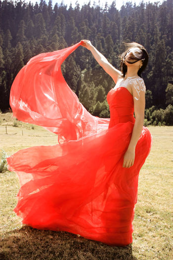 Woman in red gown standing on field at forest