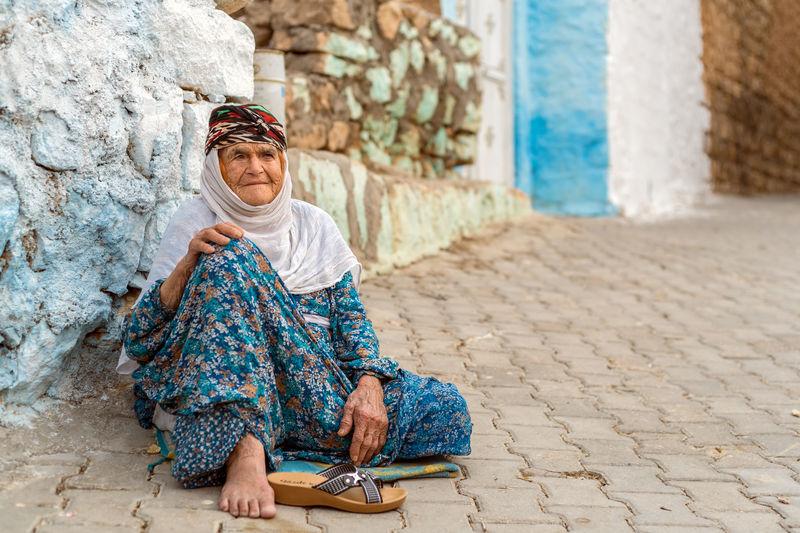 Full length of senior woman sitting against wall