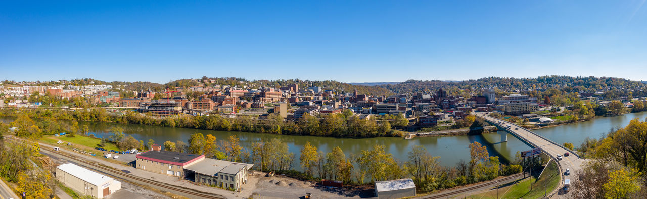 Panoramic view of river and buildings against clear blue sky
