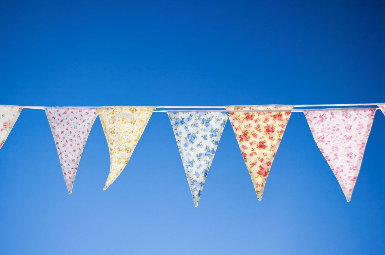 Low angle view of bunting flags hanging against clear blue sky