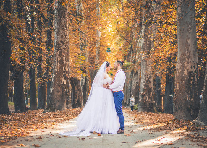 Rear view of couple walking in forest during autumn