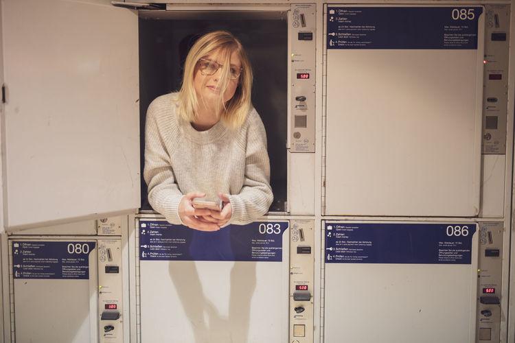 Portrait of young woman lying down in locker