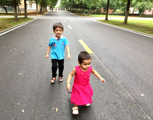 Siblings Walking On Road