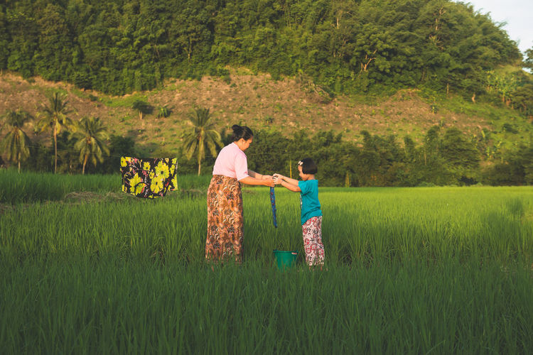 Mother and Daughter in rural Asia are helping to dry their clothes in the forest. Adult Bonding Child Couple - Relationship Emotion Family Females Field Full Length Grass Green Color Land Love Men Nature Outdoors Plant Positive Emotion Standing Togetherness Tree Two People Women