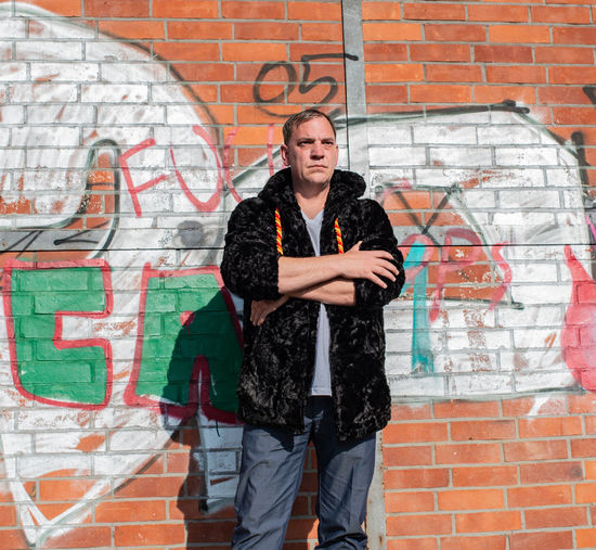 Fashionable mature man standing against graffiti wall