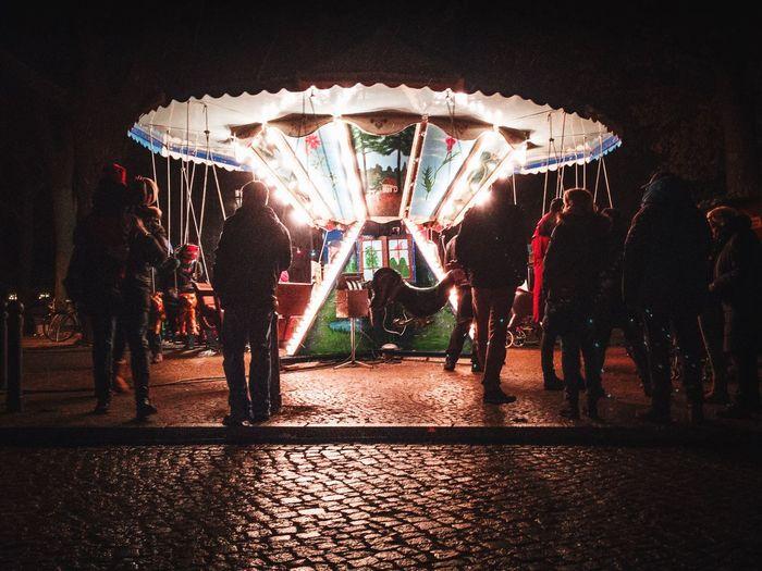 People at amusement park ride at night
