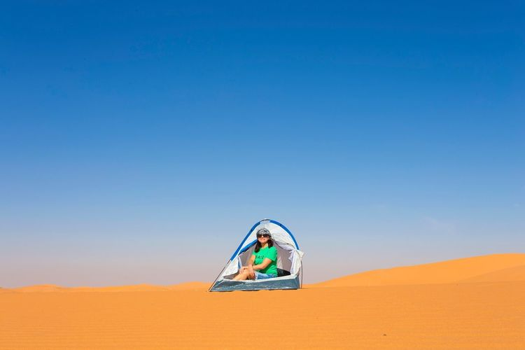 Mature woman sitting in tent on sand at desert against clear blue sky