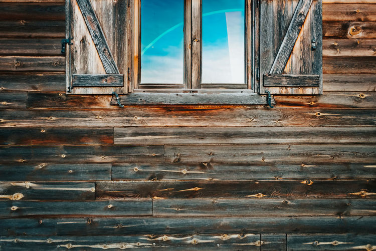 Low angle view of window on old wooden wall