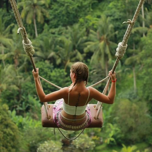 Rear view of woman holding rope while sitting on swing against trees