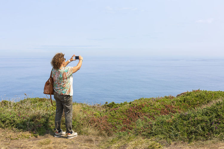 Rear view of woman photographing sea against sky