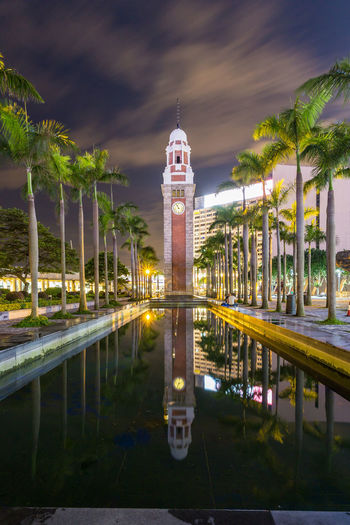 Clock tower reflecting in pond amidst palm trees at night