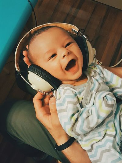 High angle view of father holding happy baby wearing headphones