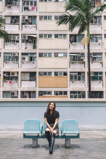 Full length portrait of woman sitting against building in city