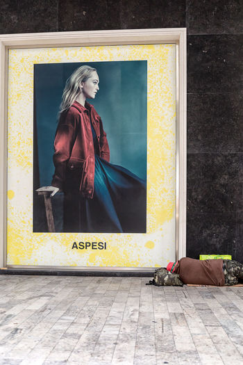 Milan, Italy - October 26, 2018: A man lies on the ground in the street at the foot of a large light sign depicting a fashion image. Full Length One Person Women Yellow Human Representation Architecture Adult Fashion Entrance Female Likeness Wall - Building Feature Door Real People Day Indoors  Young Adult Lifestyles Clothing Homeless Homelessness