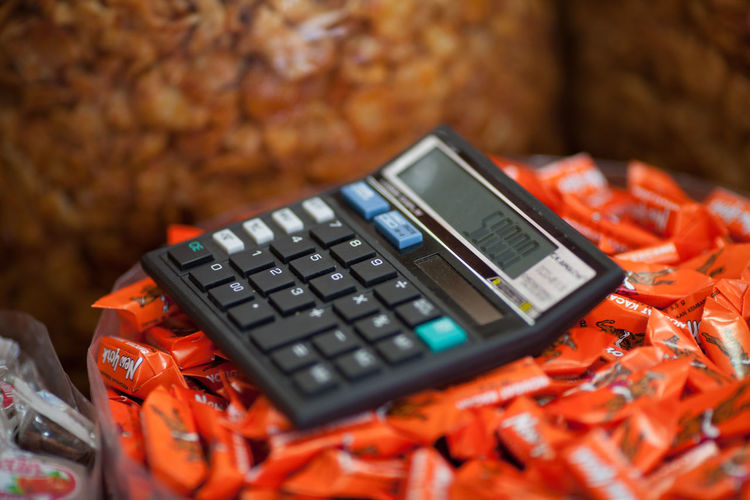 Close-Up of Calculator On Stacks of Chocolates In Shop