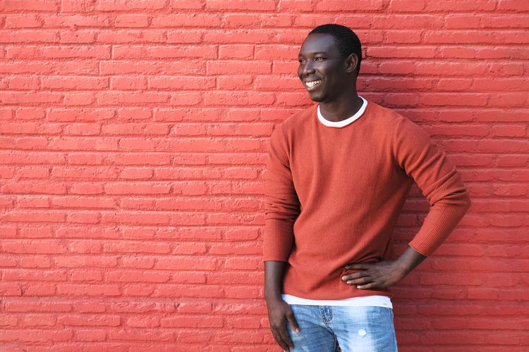 Full length of young man standing against red wall