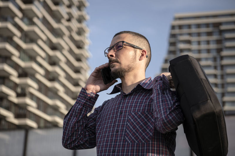 Low angle view of man talking over smart phone against buildings